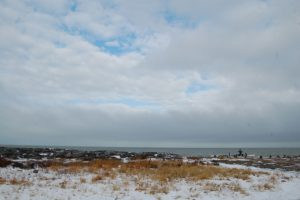 View of sea over snowy grass and beach